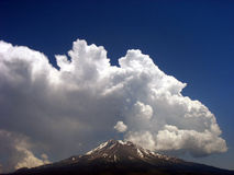 Billowing clouds over mountain peak Royalty Free Stock Image