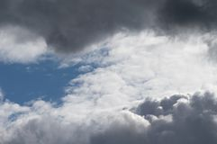 Billowing grey white clouds with blue sky. Stormy weather. Stormy weather. Moody cloudscape with both dark grey clouds and contrasting brightly lit white clouds royalty free stock photo