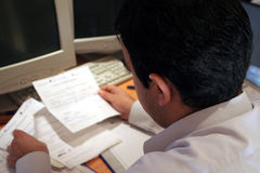 Bills, bills, bills. A young man checking the household bills Royalty Free Stock Photography