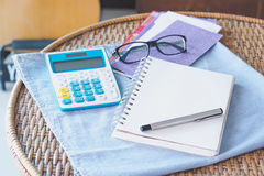 Bills expenses with calculator glasses pen and book on top of ra Royalty Free Stock Image