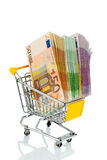 Bills in a shopping cart. Euro bank notes in a shopping cart icon photo for purchasing power, shopping, money printing and inflation Royalty Free Stock Photos