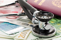 Bills with stethoscope and passport Stock Image