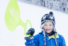 Young boy holding a sledge Stock Images