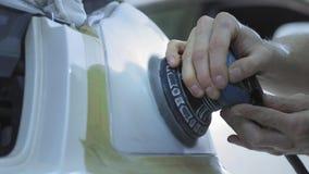 Billykta som polerar, bearbeta av billjus En bilservicearbetare polerar billyktan av en passagerarebil med a stock video