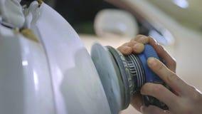 Billykta som polerar, bearbeta av billjus En bilservicearbetare polerar billyktan av en passagerarebil med a arkivfilmer