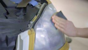 Billykta som polerar, bearbeta av billjus En bilservicearbetare polerar billyktan av en passagerarebil lager videofilmer