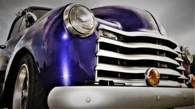 Billyktan och gallret av en purpurfärgad antik amerikan väljer upp lastbilen royaltyfri foto