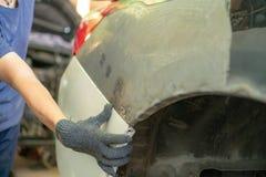 Bilmekaniker i de tjänste- reparera bucklorna för bil på bilkroppen royaltyfri fotografi