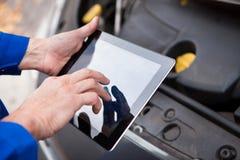 Bilmekaniker som använder den digitala minnestavlan royaltyfria foton