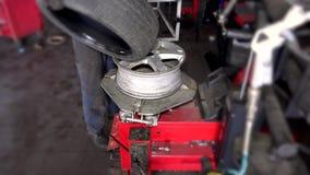 Bilmekaniker som använder special utrustning för att ändra gummihjul i garage lager videofilmer