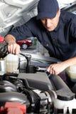 Bilmekaniker som arbetar i service för auto reparation. royaltyfri bild