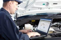 Bilmekaniker som arbetar i service för auto reparation. royaltyfri foto
