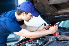 Bilmekaniker som arbetar i service för auto reparation royaltyfri foto