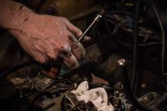 Bilmekaniker som arbetar på motorn Arkivfoto