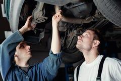 bilmekaniker som reparerar två Arkivfoton