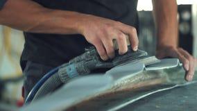 Bilmekaniker som sandpapprar bilen lager videofilmer