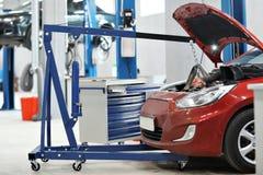 Bilmekanikern en kran tog bort motorn från bilen reparera automatiskn i billager Royaltyfria Foton