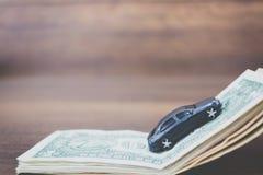 Bilmodell på dollarsedlar på träbakgrund Royaltyfri Fotografi