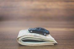 Bilmodell på dollarsedlar på träbakgrund Arkivbild