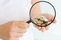 Bilmodell under förstoringsglaset i kvinnahanden som föreslår bilsökande Arkivfoto