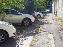 Bilparkering på den brutna trottoaren i Chisinau arkivbilder