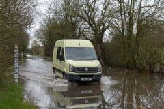 Bilpasserande till och med den översvämmade vägen med varning och mätamåttet Royaltyfria Bilder