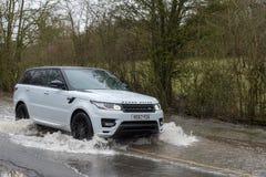 Bilpasserande till och med den översvämmade vägen med varning och mätamåttet Royaltyfri Bild