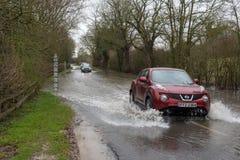 Bilpasserande till och med den översvämmade vägen med varning och mätamåttet Royaltyfria Foton