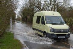 Bilpasserande till och med den översvämmade vägen med varning och mätamåttet Arkivfoto