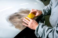 Bilreparation i bilservice Låssmeden rusar bildetaljen, händer stänger sig upp royaltyfri foto