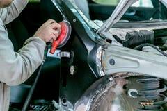 Bilreparation i bilservice Mekanikerarbetarrepairman som sandpapprar den polerande bilkroppen och f?rbereder bilen f?r att m?la u royaltyfri fotografi