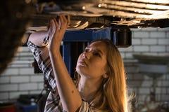 Bilreparationsservice Ungt sexigt mekanikerkvinnaanseende under bilen som rymmer en skiftnyckel och ser upp arkivfoton