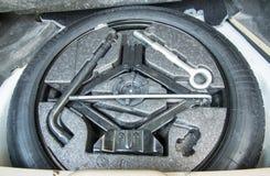 Bilreservdäcket med borttagningshjälpmedel royaltyfria foton