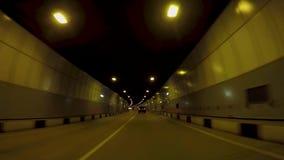 Bilritter på asfalttunnelen plats Härlig cityscape av den nya vägtunnelen med trafik i ljus av gula lyktor arkivfilmer