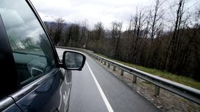 Bilritter på bergspolningsvägen Sidospegeln av bilkörning längs den spolande bergvägen reflekterar träd och molnig himmel arkivfilmer