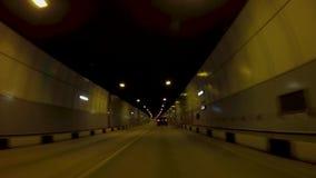 Bilritter p? asfalttunnelen plats H?rlig cityscape av den nya v?gtunnelen med trafik i ljus av gula lyktor arkivfilmer