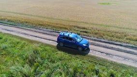 Bilritterna längs vetefälten Härligt landskap från höjden Foto från en höjd Royaltyfria Bilder