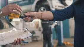 Bilseminarium - klienten ger tangenterna av bilen för mekaniker royaltyfri bild
