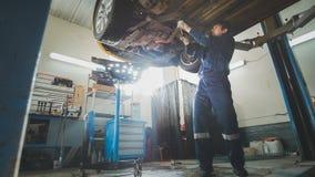 Bilservice - en mekaniker kontrollerar upphängningen av bilen, bred vinkel arkivbild