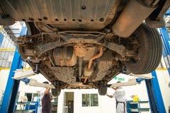 Bilservice - en mekaniker kontrollerar upphängningen av SUV, bred angl royaltyfri bild