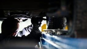 Bilservice - mekaniker som slår in den funktionsdugliga apparaten under bilbotten fotografering för bildbyråer
