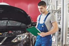 Bilservice-, reparations-, underhålls- och folkbegrepp - man eller smed för auto mekaniker med skrivplattan på seminariet arkivbild