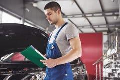 Bilservice-, reparations-, underhålls- och folkbegrepp - man eller smed för auto mekaniker med skrivplattan på seminariet royaltyfria bilder