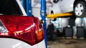 Bilservice - två mekaniker som står nära lyft fotografering för bildbyråer