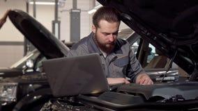 Bilservicearbetare som använder bärbara datorn, undersökande motor av en bil arkivfilmer