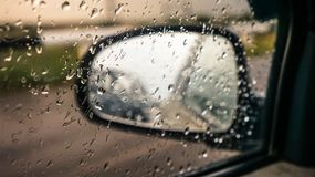 Bilspegel till och med exponeringsglas med regndroppar fotografering för bildbyråer