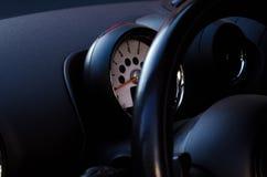 Bilstyrninghjul och takometer arkivfoto