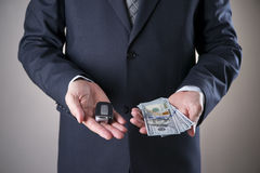 Biltangent- och hundra-dollar räkningar i händerna av en affärsman Arkivbilder