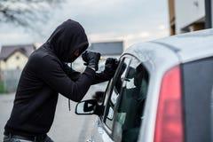 Biltjuv som försöker att bryta in i en bil med en skruvmejsel royaltyfria bilder