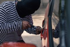Biltjuv som försöker att låsa en bil upp vid skruvmejseln royaltyfria foton